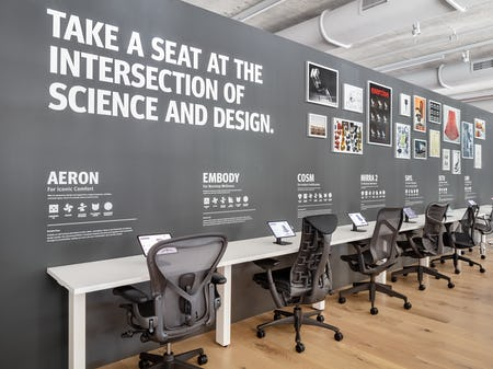 A row of gray office chairs including Aeron, Embody, Cosm, and Mirra 2, line the Performance Seating display in the Fulton Market Showroom.