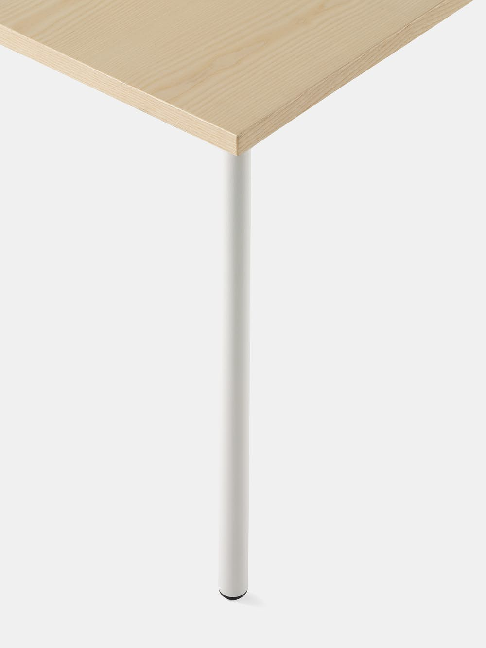 OE1 Rectangular Table with light brown surface and white legs with an up close view of the rounded leg.