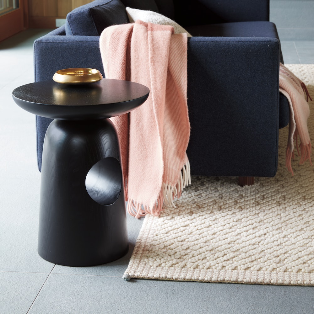 A black Hew Side Table placed at the arm of a sofa in a comfortable residential environment.