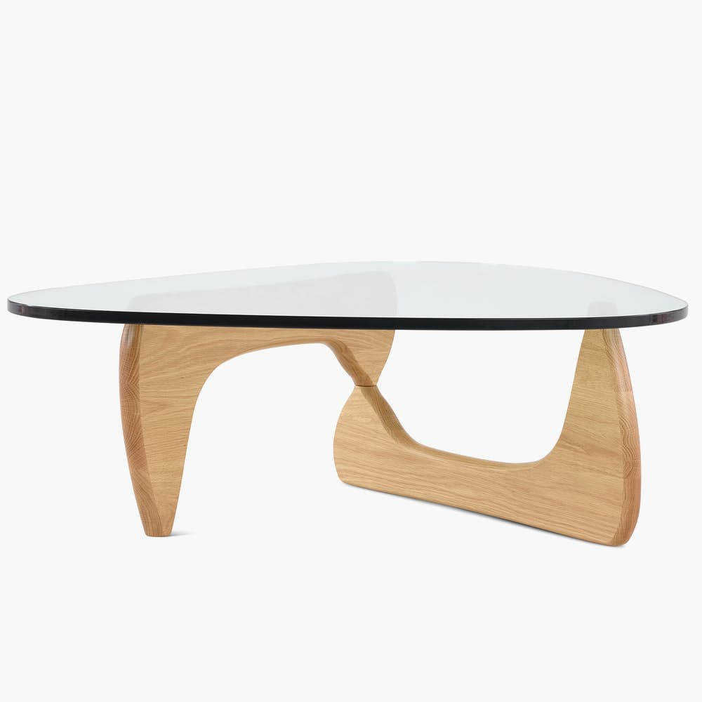 A Noguchi Table with light wood base and glass top