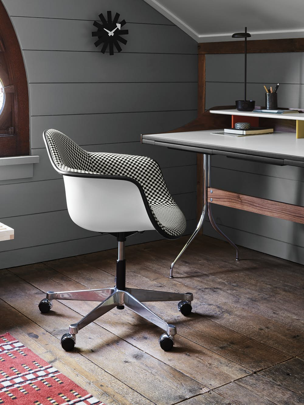 An Eames Molded Fiberglass Chair upholstered in a gray textile, seated in front of a Nelson Swag Leg Desk in an individual workstation setting.