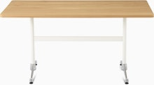 An oak Eames T-Leg Table with white legs and chrome feet.