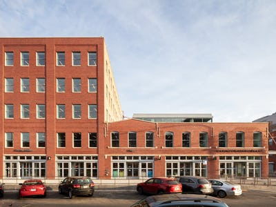 A straight-on view of the red brick exterior of the Herman Miller Group Fulton Market Showroom on a sunny afternoon.