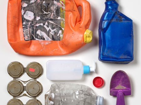 Seven  pieces of colorful, ocean-bound plastic trash laid out in a square pattern on a white backdrop.