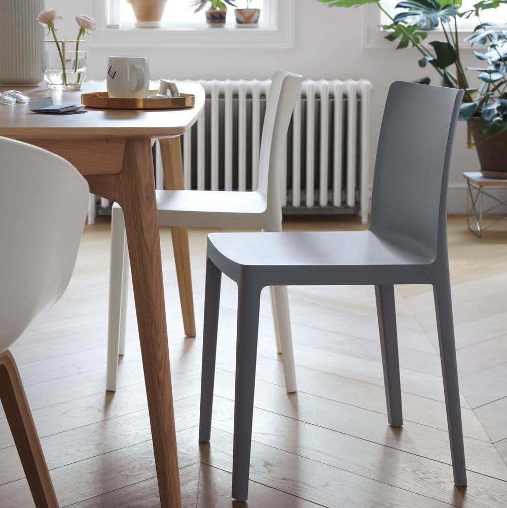 Two Élémentaire Chairs next to a dining table.