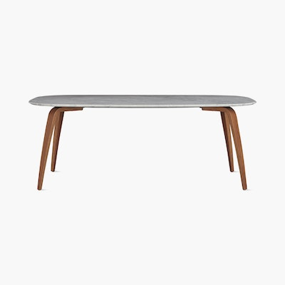 A carrara elliptical Organic Dining Table with walnut base viewed from the front