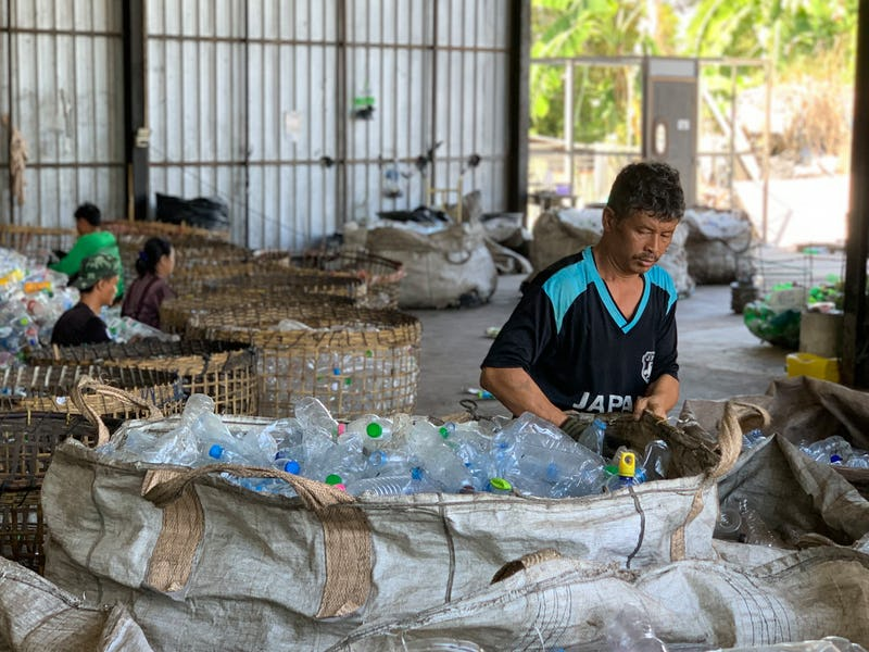 A man sorting plastic bottles in a warehouse.